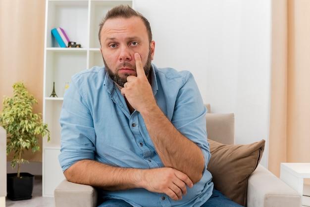 Уверенный в себе взрослый славянский мужчина сидит на кресле, опуская веко в гостиной