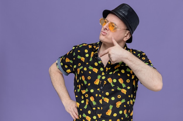 Uomo slavo adulto fiducioso con cappello a cilindro nero che indossa occhiali da sole che guardano e puntano a lato
