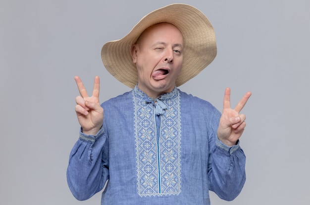 Confident adult slavic man with straw hat and in blue shirt blinks his eye and gestures victory sign