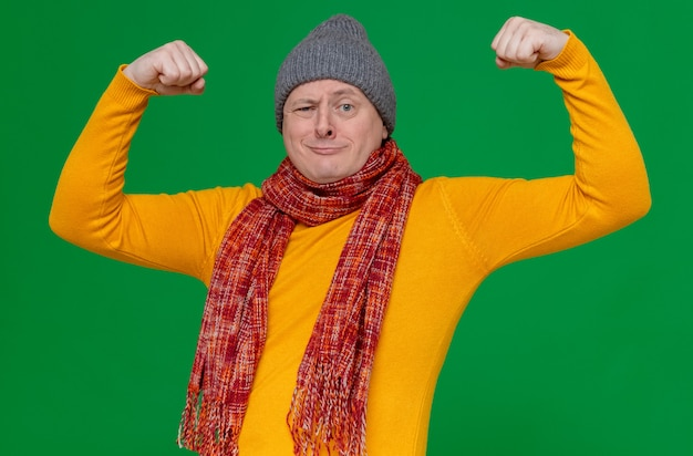 Fiducioso uomo slavo adulto con cappello invernale e sciarpa intorno al collo tendendo i suoi bicipiti