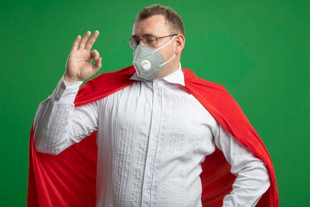 Уверенный взрослый славянский супергерой в красном плаще в очках и защитной маске, держащий руку на талии, глядя вперед, делает знак ок, изолированный на зеленой стене