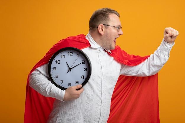 Уверенный взрослый славянский супергерой в красной накидке в очках, держащий часы, протягивающий кулак, смотрящий в сторону, изолированную на оранжевой стене