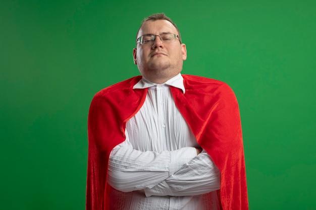 복사 공간 녹색 벽에 고립 된 닫힌 자세로 서 안경을 쓰고 빨간 케이프에서 자신감 성인 슬라브 슈퍼 히어로 남자