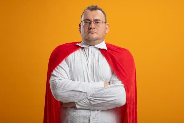 복사 공간 오렌지 벽에 고립 된 닫힌 자세로 서 안경을 쓰고 빨간 케이프에서 자신감 성인 슬라브 슈퍼 히어로 남자