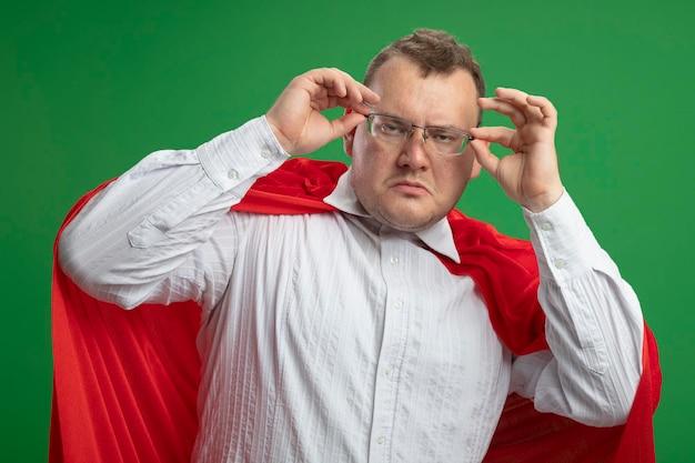 Fiducioso uomo adulto supereroe slavo in mantello rosso con gli occhiali che li afferra guardando davanti isolato sulla parete verde