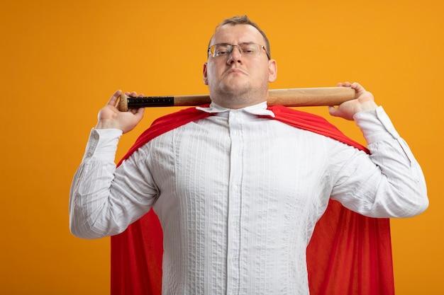 Uomo adulto sicuro del supereroe slavo in mantello rosso con gli occhiali che tiene la mazza da baseball dietro il collo isolato sulla parete arancione