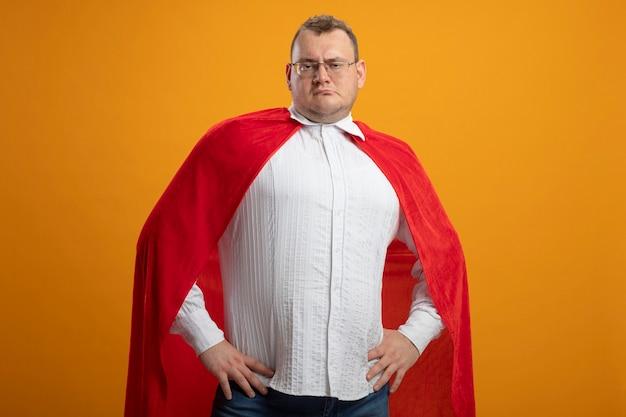Fiducioso adulto supereroe slavo uomo in mantello rosso con gli occhiali tenendo le mani sulla vita isolato sulla parete arancione con copia spazio