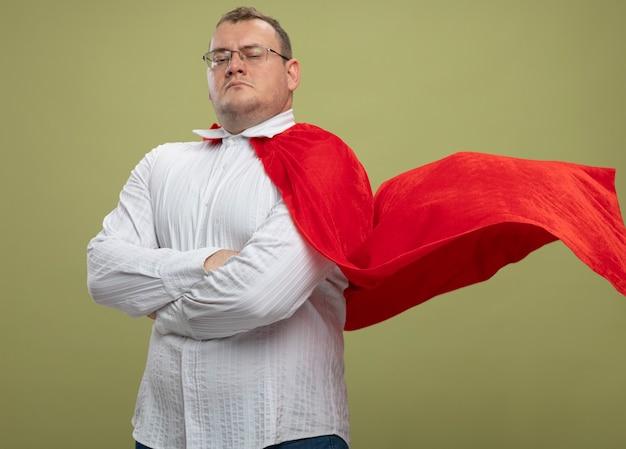Fiducioso adulto supereroe slavo uomo in mantello rosso con gli occhiali che guarda l'obbiettivo isolato su sfondo verde oliva