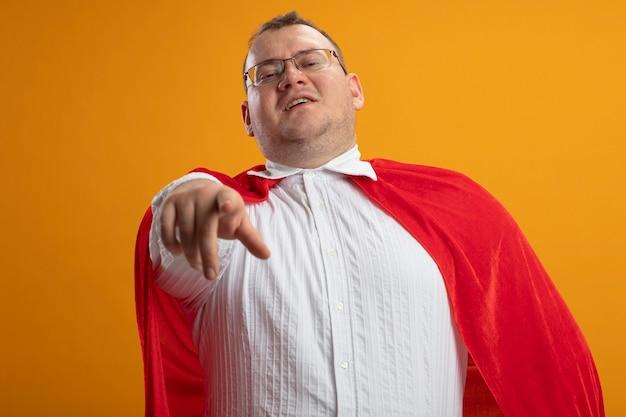 Uomo adulto sicuro del supereroe slavo in mantello rosso con gli occhiali alla ricerca e indicando isolato sulla parete arancione