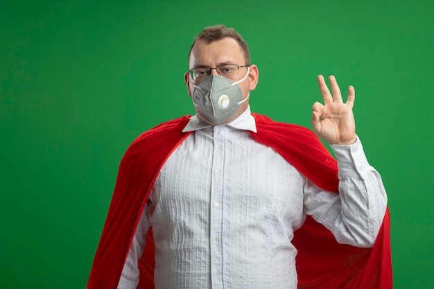 Confident adult slavic superhero man in red cape wearing glasses and protective mask  doing ok sign isolated on green wall with copy space