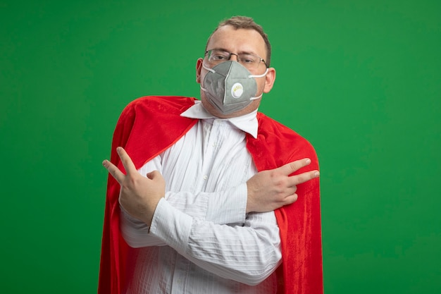 Fiducioso adulto supereroe slavo uomo in mantello rosso con gli occhiali e maschera protettiva tenendo le mani incrociate facendo segno di pace isolato sulla parete verde con lo spazio della copia