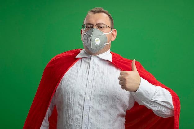 Fiducioso adulto supereroe slavo uomo in mantello rosso con gli occhiali e maschera protettiva che mostra il pollice in alto isolato sulla parete verde