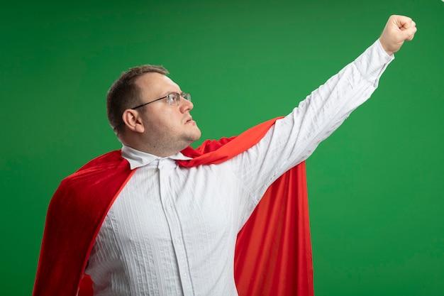 Fiducioso uomo adulto supereroe slavo in mantello rosso con gli occhiali alzando il pugno guardandolo isolato sulla parete verde