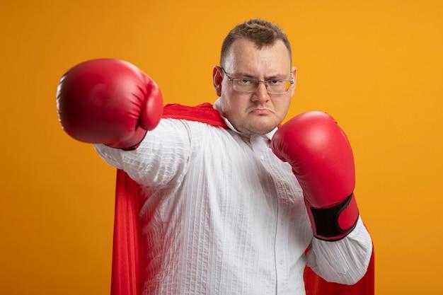オレンジ色の壁に分離されたボクシングのジェスチャーをしている正面を見て眼鏡とボクシンググローブを身に着けている赤いマントの自信を持って大人のスーパーヒーローの男