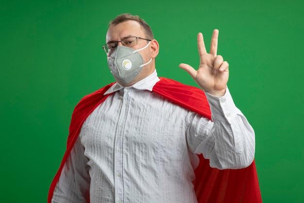 緑の壁に隔離された手で3つを示す正面を見て眼鏡と保護マスクを身に着けている赤いマントの自信を持って大人のスーパーヒーローの男