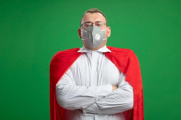 녹색 벽에 고립 된 전면을보고 닫힌 자세로 서 안경과 보호 마스크를 착용하는 빨간 케이프에서 자신감 성인 슈퍼 히어로 남자