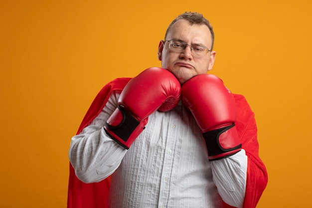 Confident adult superhero man in red cape wearing glasses and box gloves keeping hands under chin looking at front isolated on orange wall