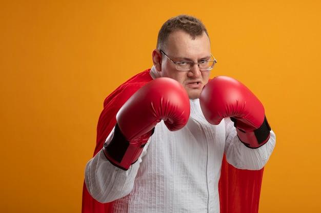 Fiducioso uomo adulto supereroe in mantello rosso con gli occhiali e guanti di scatola guardando davanti facendo gesto di boxe isolato sulla parete arancione