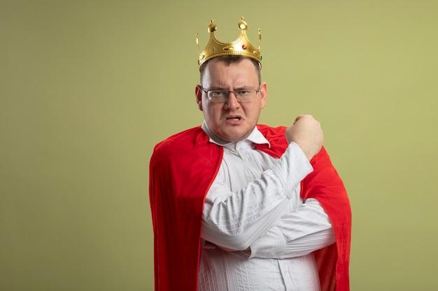 Fiducioso uomo adulto supereroe in mantello rosso con gli occhiali e corona che stringe il pugno guardando davanti isolato sulla parete verde oliva