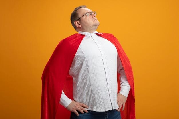 Fiducioso uomo adulto supereroe in mantello rosso con gli occhiali tenendo le mani sulla vita guardando il lato isolato sulla parete arancione