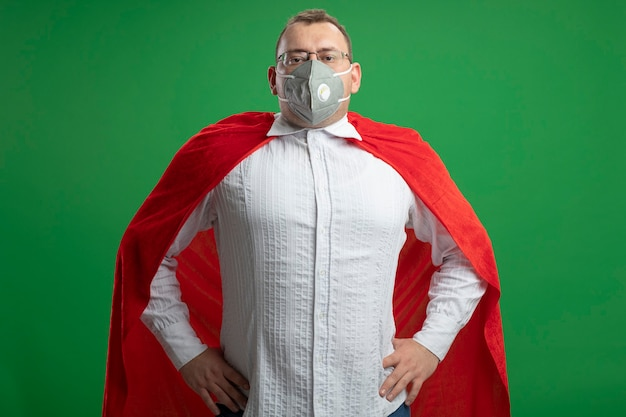 Confident adult superhero man in red cape wearing glasses and protective mask looking at front keeping hands on waist isolated on green wall