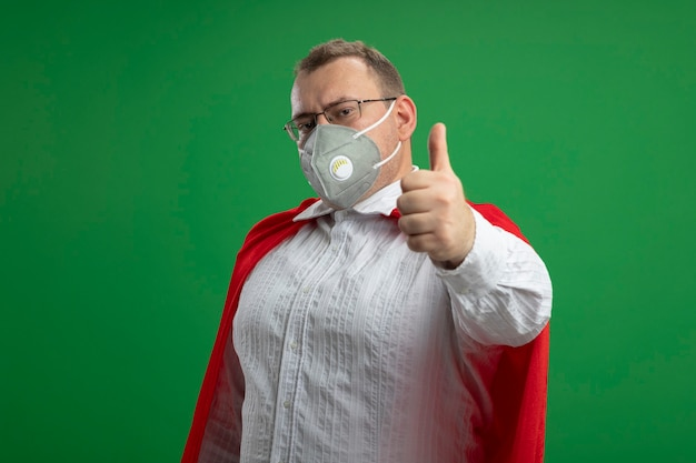 Confident adult superhero man in red cape wearing glasses and protective mask looking at front showing thumb up isolated on green wall