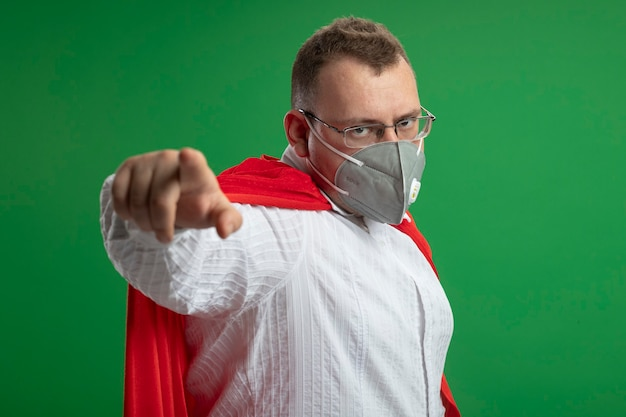 Confident adult superhero man in red cape wearing glasses and protective mask standing in profile view looking and pointing at front isolated on green wall
