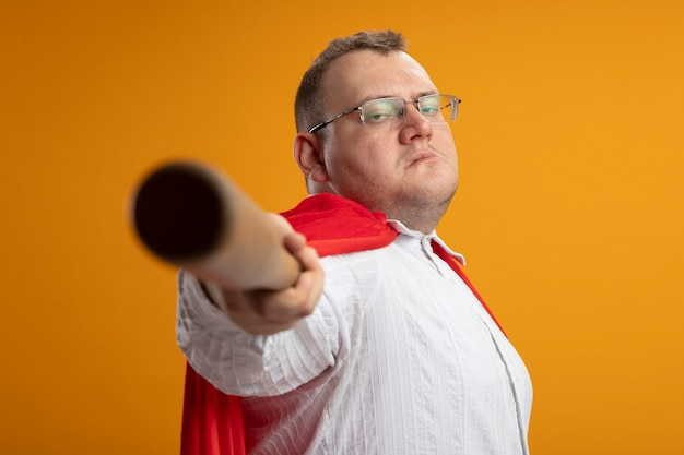 Confident adult superhero man in red cape wearing glasses standing in profile view looking at front stretching out baseball bat towards front isolated on orange wall