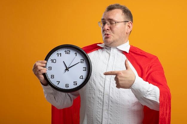 Fiducioso uomo adulto supereroe in mantello rosso con gli occhiali che sbatte le palpebre davanti tenendo e indicando l'orologio isolato sulla parete arancione