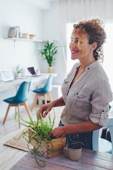 自信を持って大人の女性は、ガーデニングの趣味の時間に自然植物の世話をしている家庭の屋内レジャー活動で居間を楽しんでいます。幸せな魅力的な女性は明るい家で時間を過ごします