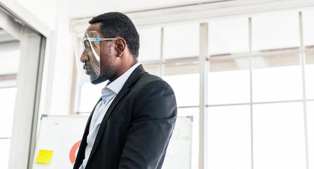 フェイスシールドを身に着け、ホワイトボードの前に立っている自信を持ってアフリカ系アメリカ人のビジネスマン