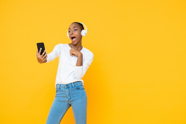 Confident african american woman wearing headphones listening to music from mobile phone in yellow isolated wall
