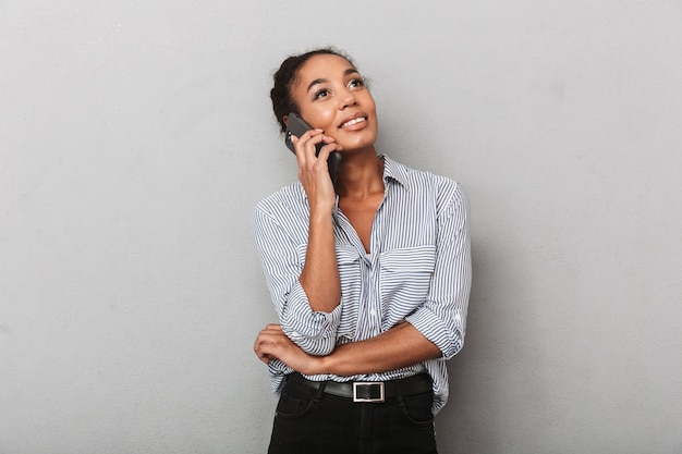 Confident african business woman wearing shirt standing isolated over gray, talking on mobile phone