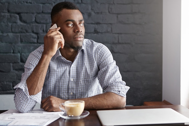 Confident african ceo of large financial company making business calls during coffee break