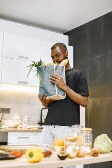 자신감 넘치는 아프리카 힙스터 남성 블로거가 부엌에 앉아 디지털 카메라로 요리하는 것에 대한 브이로그를 기록하고 있다