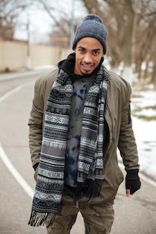 Uomo africano sicuro che sta sulla strada nell'inverno