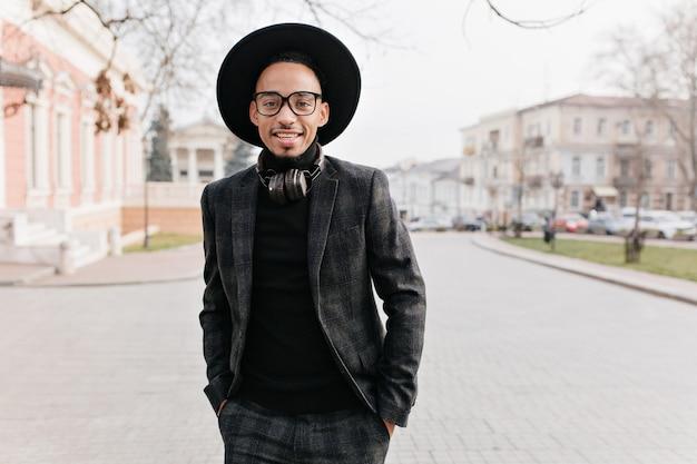 주머니와 관심이 얼굴 표정에 손으로 서 자신감이 아프리카 남자. 아침에 거리에서 누군가를 기다리고 화려한 흑인 남성 모델의 야외 사진.