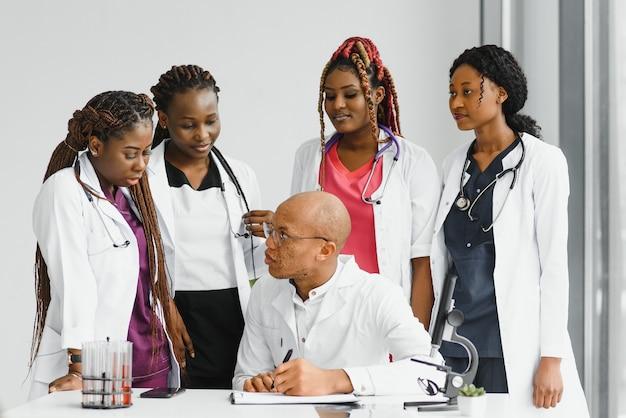 Уверенный африканский врач и портрет коллег в больнице