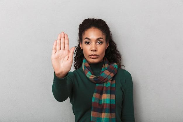Уверенная африканская женщина в свитере стоя, показывая стоп-жест