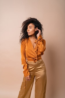 Confident african woman with perfect curly hairs in casual orange blouse and golden pants posing on beige wall.