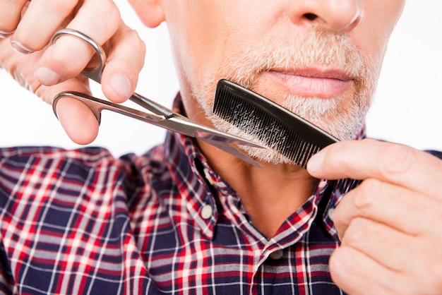 自信を持って老人がひげを切る