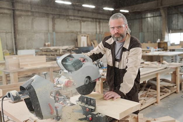 Уверенный в себе пожилой профессионал в очках и спецодежде стоит на рабочем месте во время резки толстой деревянной доски электрической пилой