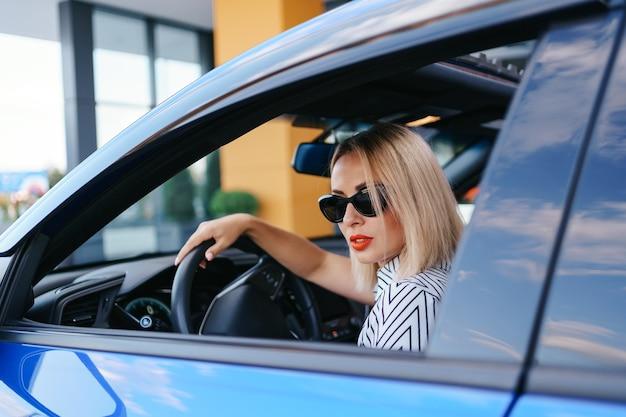 Уверенная и красивая женщина в солнечных очках. вид сзади привлекательной молодой женщины в повседневной одежде за рулем автомобиля