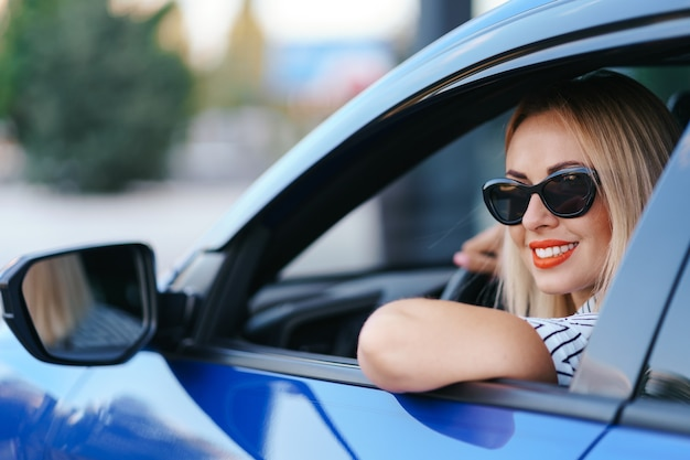 サングラスで自信を持って、美しい女性。車を運転してカジュアルな服装で魅力的な若い女性の後姿