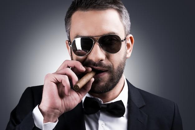 自信と偉そう。灰色の背景に立っている間葉巻を吸う正装とサングラスのハンサムな成熟した男の肖像画