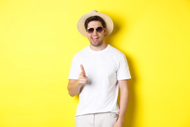休暇中の自信を持って生意気な男があなたとイチャイチャ、カメラに指を向けてウインク、サングラス、黄色の背景の夏の帽子をかぶっています