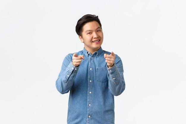 中かっこ、笑顔、人を励ます、誰かを選ぶようにカメラに指を向ける、または幸運な勝者を祝福する、白い背景に立っている自信を持って陽気なアジアの若い男。