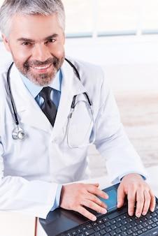 자신감 있고 경험 많은 의사. 자신의 작업장에 앉아 노트북 작업을 하고 웃고 있는 자신감 있는 성숙한 회색 머리 의사의 상위 뷰