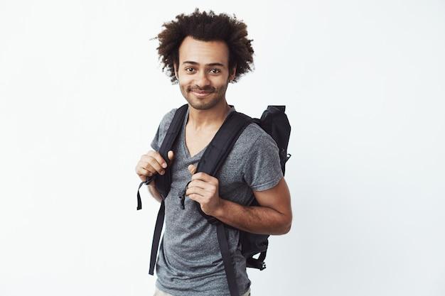 ヒッチハイクまたは山でのハイキングに行く準備ができて笑っているバックパックで自信を持って、幸せなアフリカの若い男。