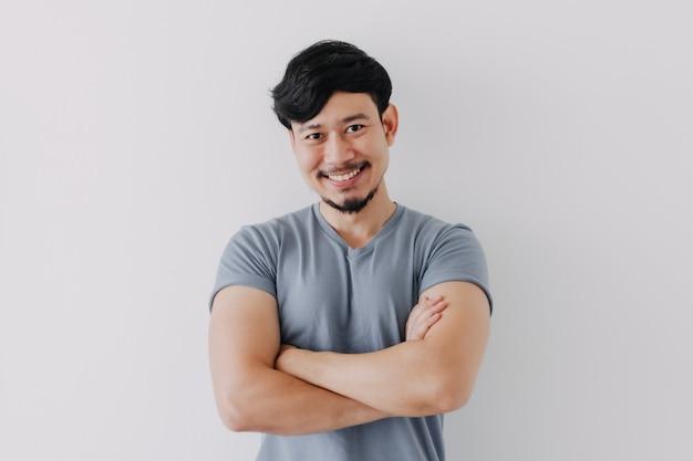 白い背景で隔離の青いtシャツの自信と幸せな男
